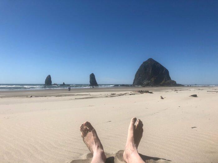 Fötter i sanden framför Haystack Rock