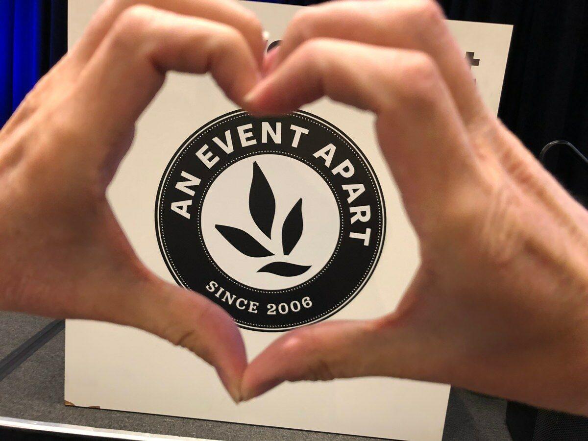 Två händer formar ett hjärta framför konferensens logotyp