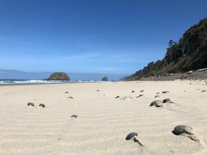 Tom strand med klippor i fjärran