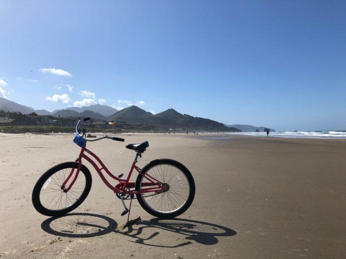 Cykel på strand med kullar i bakgrunden