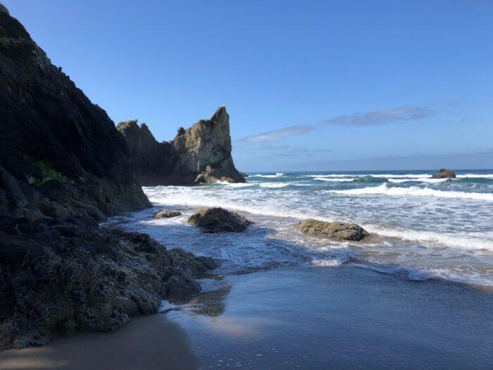 Högt vatten vid klippor vid ända på strand